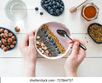 Eating healthy breakfast bowl. Buckwheat smoothie porrige, fresh berries, seeds and nuts, bee pollen in white ceramic bowl in woman hands on table. Clean eating, dieting,detox, vegetarian food concept