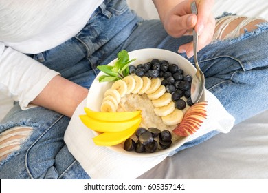 Eating healthy breakfast bowl porridge oats granola, seeds, fresh and dry fruits and honey in blue ceramic bowl in woman' s hands. Clean eating, dieting, detox, vegetarian food concept