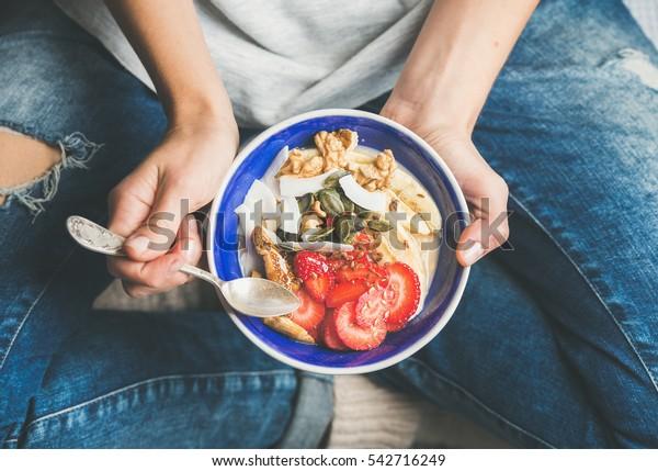 健康に良い朝食のボウルを食べる。青い陶器の鉢に入ったヨーグルト、グラノーラ、種、生鮮で乾燥した果実、蜂蜜。清潔な食事、ダイエット、デトックス、ベジタリアンの食べ物のコンセプト