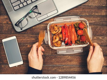 Eating healthy business lunch at workplace. Baked vegetables and chicken lunch box on working desk with laptop smartphone and glasses.