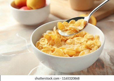 Eating of healthy cornflakes with milk from bowl on table, closeup