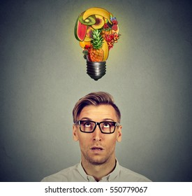 Eating healthy and diet tips concept. Man looking up at fruit light bulb above head isolated on gray wall background