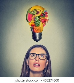 Eating healthy idea and diet tips concept. Closeup portrait headshot woman looking up light bulb made of fruits above head on gray wall background.