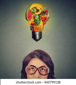 Eating healthy idea and diet tips concept. Closeup portrait headshot woman in glasses looking up light bulb made of fruits above head isolated on gray wall background.
