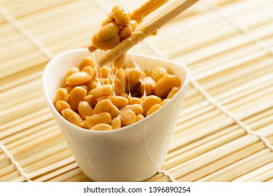 Eating healthy traditional japanese fermented soybeans called natto with chopsticks