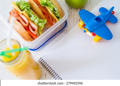 Eating lunch - notepad, sandwich, orange juice, apple, toy, white wood background, top view