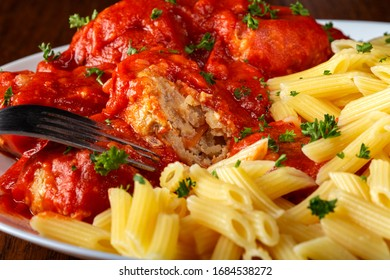 Eating meatballs in tomato sauce with pasta - close up view