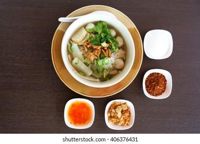 Eating noodle on table and cilantro,fried garlic,spring onion,sugar,chilli powder,vinegar,cane sugar