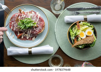 Eating out, top down view of lunch with ceasar salad and beef carpaccio sandwich in luxury lunch space, green placemats and white napkins