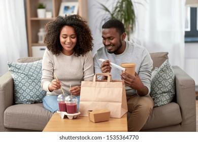 食事と人のコンセプト – 家で持ち帰り用の食べ物と飲み物を持つアフリカ系の幸せな夫婦
