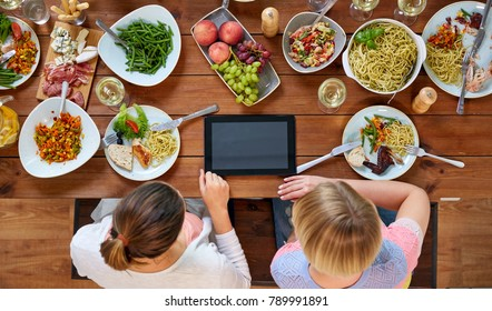 eating, people and technology concept - women with tablet pc computer sitting at table full of food