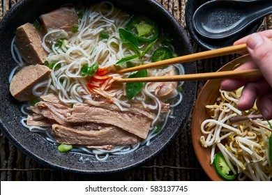 eating pho with brisket and sriracha sauce from overhead view