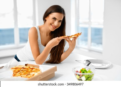 Eating Pizza. Portrait Of Attractive Caucasian Smiling Healthy Woman Eating Italian Food In Modern Kitchen At Home. Fast Food Nutrition. Dieting, Diet And Lifestyle Concept.
