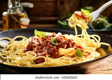 Eating a plate of tasty Italian spaghetti topped with a beef and tomato sauce garnished with basil and parmesan cheese with a mouthful twirled on a fork above