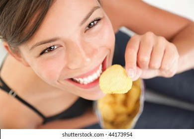 Eating potato chips / crisps.  Cute woman having a junk food snack while looking up at camera. Adorable mixed race chinese / caucasian model.