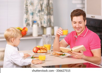 Eating and reading. Dad having breakfast with his beloved son and reading a book at the same time.