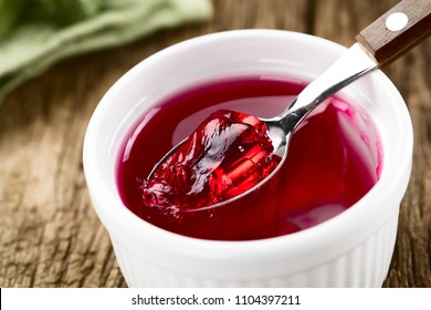 Eating red jelly or jello, spoonful of jelly on the top (Selective Focus, Focus in the middle of the image)