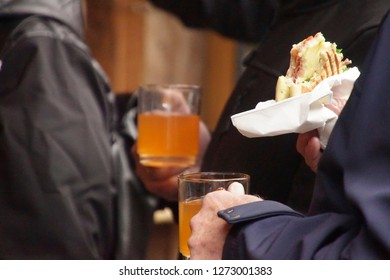 Eating a sandwich with hot mulled cider at the Christmas market of Cologne, Germany