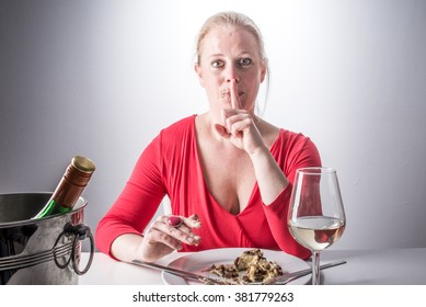 Eating secretly - Young woman eating chocolate and drinking white wine - Over eating - Drinking and eating too much - Diet and resisting - Dieting concept - Eating and hiding - Sneak and cheat