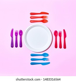 Eating set from disposable plastic cutlery, serving around paper white plate on a pastel pink background with copy space. Flat lay.