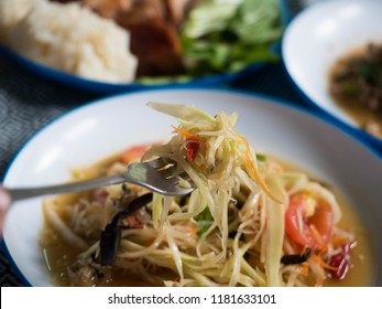 Eating Som Tum (Thai Spicy Green Papaya Salad) with fork. This dish originally comes from Isan, North eastern part of Thailand. Very classic, iconic and must try food.