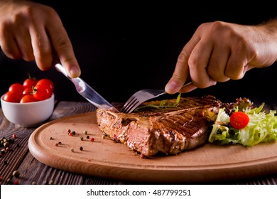 eating stake from plate with fork and knife man hands