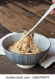 eating stir-fried noodles with chopstick on wooden table.