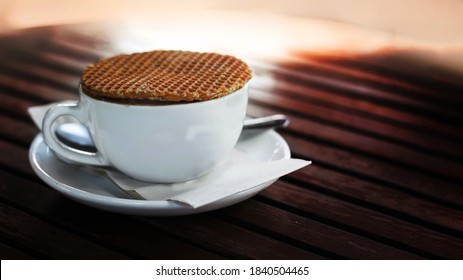 eating stroopwafel dessert with coffee on wood table in morning time
