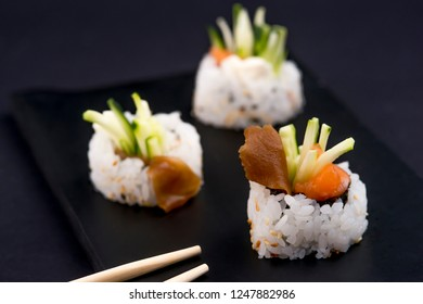 Eating Sushi with chopsticks. Sushi roll japanese food in restaurant. Philadelphia Hosomaki roll set with salmon, vegetables, flying fish roe and caviar close up. Japan restaurant menu