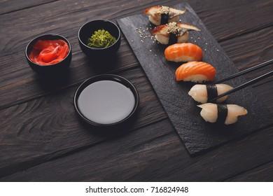Eating sushi. Japanese food restaurant, unagi and salmon sushi on dark background. Closeup on black wood