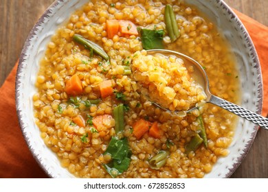 Eating tasty lentil dish with vegetables on wooden table, closeup