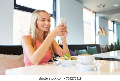 eating, technology, communication and leisure concept - happy woman with smartphone, salad and coffee for lunch at restaurant