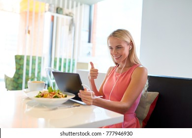 eating, technology, people and leisure concept - happy young woman with tablet pc computer and food having video conference at restaurant
