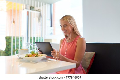 eating, technology, people and leisure concept - happy young woman with tablet pc computer, earphones and food at restaurant