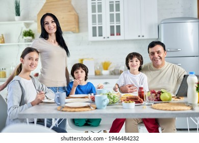 Eating together. Smiling hispanic parents spending time with their little children, having breakfast together at home