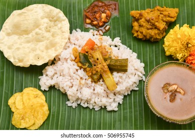 Eating traditional Onam sadhya using right hand, boiled red Kerala rice, served with curries Parippu, Sambar, Pulisseri, Kaalan, Avial, Olan, Pachadi, Papadum, Payasam in banana green leaf