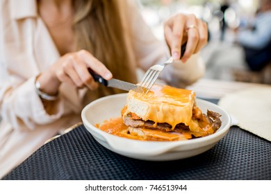 Eating traditional portuguese meat sandwich with tomato sauce called francesinha at the restaurant in Porto city