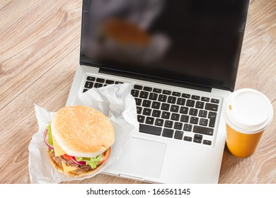 Eating at work place   -  fast food (burger and coffee)  near laptop