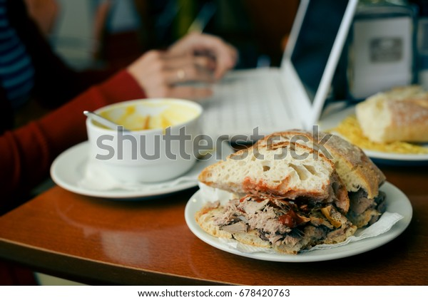 Eating and working. Closeup on busy professional woman typing document on laptop pc computer in cafe. Businessperson using information electronic communication, browsing mobile wifi internet