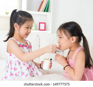 Eating yogurt. Happy Asian children eating yoghurt at home. Beautiful sisters . Healthcare concept.