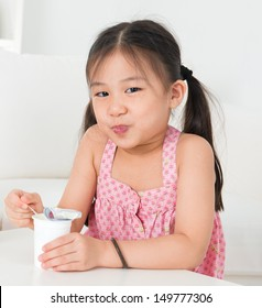 Eating yogurt. Happy Asian kid eating yoghurt at home. Beautiful child. Healthcare concept.