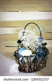 Eatser image includes a green, wire basket with colorful spotted eggs and baby's breath on a rustic wooden background. Ceramic bunny and vignette added. Copy space. Vertical.