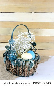 Eatser image includes a green, wire basket with colorful spotted eggs and baby's breath on a rustic wooden background.