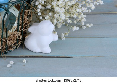 Eatser image includes a green, wire basket with colorful spotted eggs and baby's breath on a rustic wooden background. Ceramic bunny and copy space.
