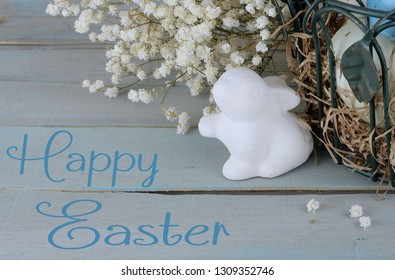 Eatser image includes a green, wire basket with colorful spotted eggs and baby's breath on a rustic wooden background. Ceramic bunny and message added