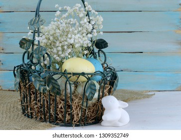 Eatser image includes a green, wire basket with colorful spotted eggs and baby's breath on a rustic wooden background. Ceramic bunny added. Copy space.