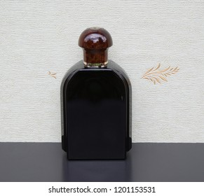 Eau de Toilette, large perfume bottle in front of the satin wallcovering Elysee