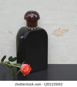 Eau de Toilette, large perfume bottle in front of the satin wallcovering Elysee decorated with an English rose