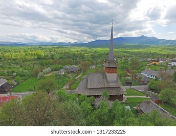 A eautiful wooden Greek-Catholic church with high spire in village of Harnicesti in Maramures county, Romania, in springtime. The Carpathian Mountains on background, aerial view. Tourist attraction.