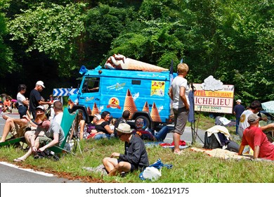 EAUX-BONNES,FRANCE-JUL 15: Tourists waiting for the cyclists while a car from the publicitary caravan is passing,on the road to Col d'AUbisuqe,during the 13 stage of Le Tour de France on July 15 2011